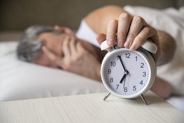 Man lying in bed turning off an alarm clock in the morning at 7a